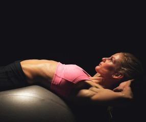 Focused Woman Exercising on a Fitness Ball