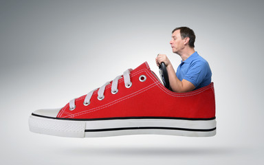Funny man car driver with a wheel in red sneaker