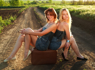 Two pretty girl on lonely road in sunset rays
