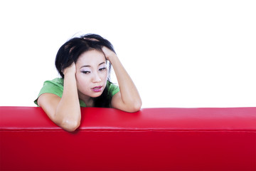 Close-up depressed female on red sofa - isolated