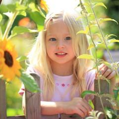 Mädchen schaut über Gartenzaun