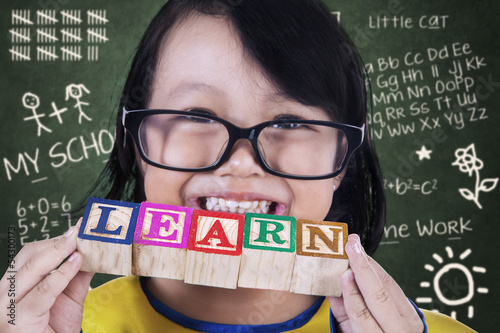 Close-up girl graduate hold learn wooden toy in class