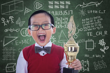 Excited student boy holding trophy in class
