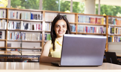 Smiling female student working with laptop in a high school libr