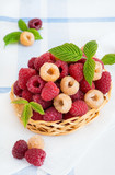 Mixed raspberries in basket over light background