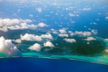Polynesia.The atoll in ocean through clouds. Aerial view