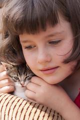 Little girl hugging kitten