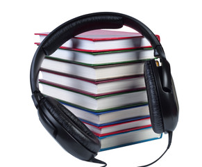 Audio headphones on a pile of books with color covers.