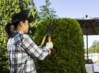 Mature woman Trimming the Hedges near her patio