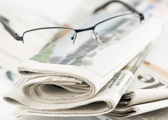 Stack of newspapers and glasses lying on table