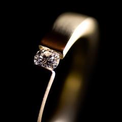 Makroaufnahme von Goldring mit Diamant vor schwarzem Hintergrund