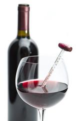 calice di vino con termometro e bottiglia su sfondo bianco