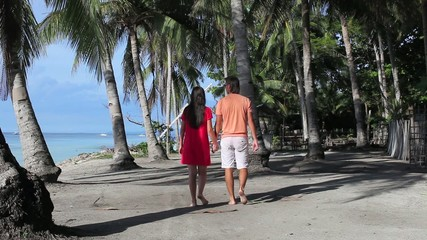 Romantic couple walk at tropical beach near palm tree in