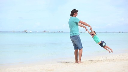 Young father and his little daughter on exotic white sand beach