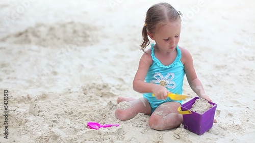 Beautiful little girl playing on tropical beach