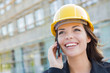 Young Female Contractor Wearing Hard Hat on Site Using Phone