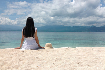 Woman with black hair sitting on a beach in the Gili Islands