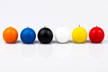 six colored candles on a white background