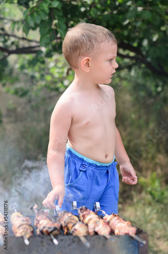 Young boy grilling kebabs on a barbecue