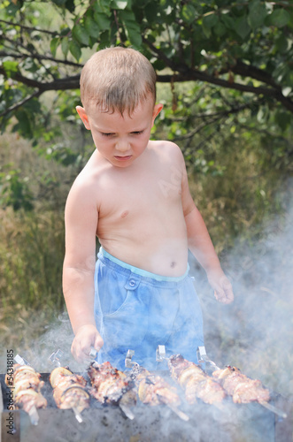Young boy cooking at a barbecue