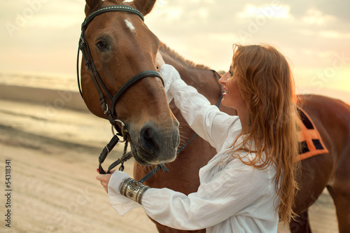 Young woman and horse on sea cost