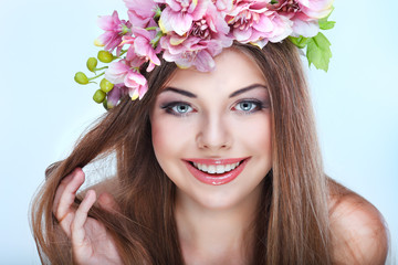 Hortrait of beautiful young girl with pink flowers