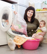 woman with baby putting clothes into washing machine