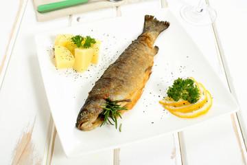 pesce trota fritta su piatto ceramica bianco