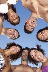 Personen am Strand im Kreis schauen nach unten