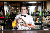 Young  barman standing in front of the bar and making cocktail.