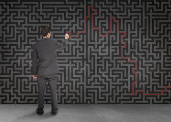 Rear view of a businessman writing a red line through black maze