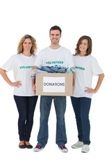 Group of volunteers holding donation box with clothes