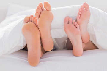 Couples feet crossed under the duvet