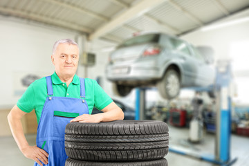 Mechanic posing on tires in front of car during automobile maint