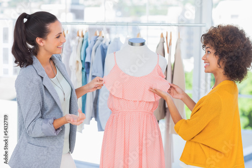 Pretty fashion designers adjusting a dress
