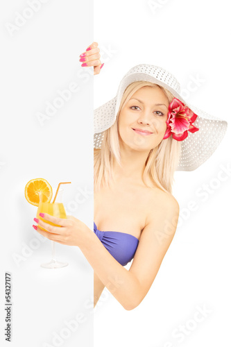 Blond woman in bikini holding a cocktail and posing behind a pan