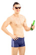 Young handsome male in swimming shorts holding a beer bottle
