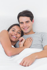 Pretty woman embracing her partner in bed
