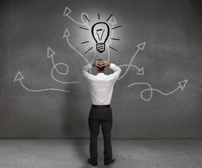 Stressed businessman looking at a light bulb