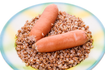 Two sausages on a plate with buckwheat