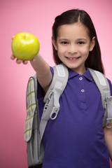 Schoolgirl with apple. Cheerful little schoolgirl holding an app