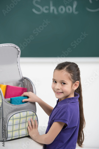 Packing her book bag. Cheerful little schoolgirl packing her boo
