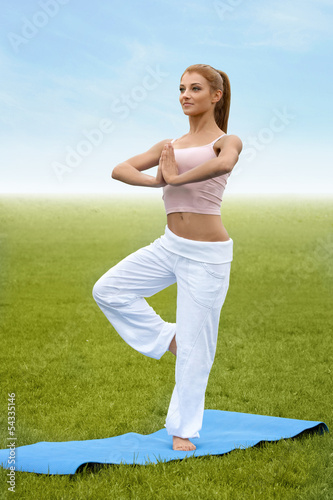 Yoga Woman. Young woman practicing morning meditation against na
