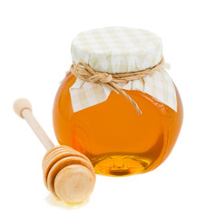 honey in glass pot and stick