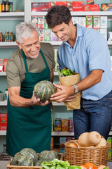 Salesman Assisting Male Customer In Shopping Vegetables