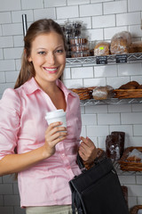 Woman Holding Coffee Cup And Bag At Store
