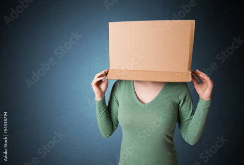 Young girl gesturing with a cardboard box on his head