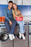 Happy Young Couple Sitting On Washing Machines