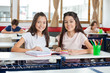 Portrait Of Happy Schoolgirls Sitting With Book At Desk
