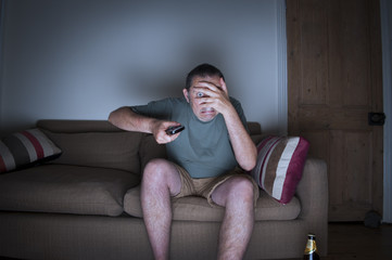 man covering face watching tv